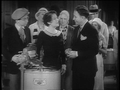 vídeos de stock e filmes b-roll de bing crosby standing with group of people by washing machine talking / short - 1931
