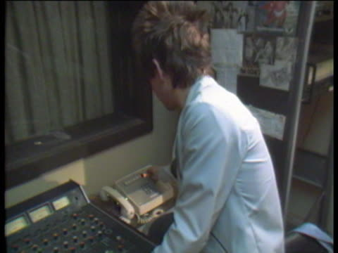 bingenheimer answering phones and talking with another dj in the studio of the kroq radio station in los angeles - pop music stock-videos und b-roll-filmmaterial