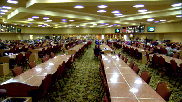 stockvideo's en b-roll-footage met ws bingo hall filled w/ long tables some people at chairs game gamble gambling lottery recreation - bingo