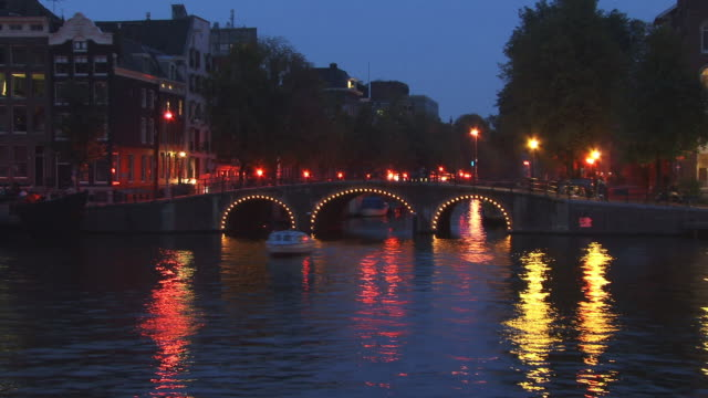 t/l, ws, binnenamstel canal illuminated at dusk, amsterdam, netherlands - olanda settentrionale video stock e b–roll