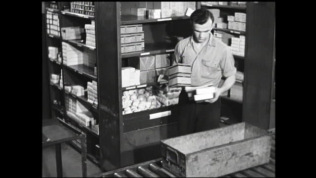 bins passing by on the conveyor belts filled with various items by workers - 1940 1949 video stock e b–roll