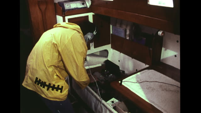 biologist & environmentalist roger payne into sailboat cabin, two crew on deck, roger putting on headphones, turning on tape recorders, sot humpback... - cetaceo video stock e b–roll