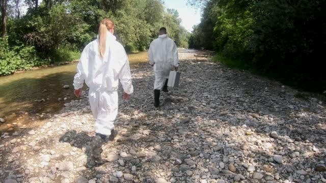 vídeos de stock, filmes e b-roll de biólogo leva água de um rio florestal para estudar a composição no laboratório - amostra científica