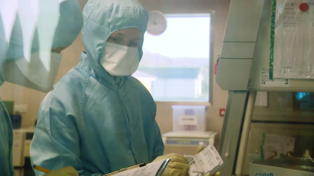 biomedical scientists wearing protective suits point at equipment and make notes on a clipboard as they research mers vaccines at the clinical... - adults only stock videos & royalty-free footage