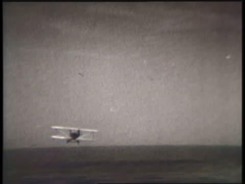 vidéos et rushes de a biplane crash-lands in a field. - image en noir et blanc