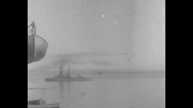 biplane flies high over battleship / pan to hanging lifeboat and plane flying low beyond / the flying boat on water / motor launch comes to stop at... - schlachtschiff stock-videos und b-roll-filmmaterial
