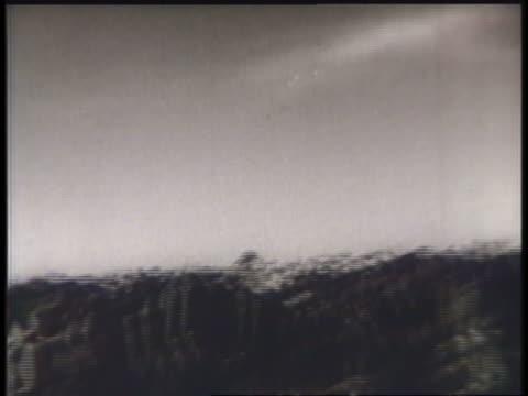 vidéos et rushes de a biplane flies low over a rugged landscape. - biplan