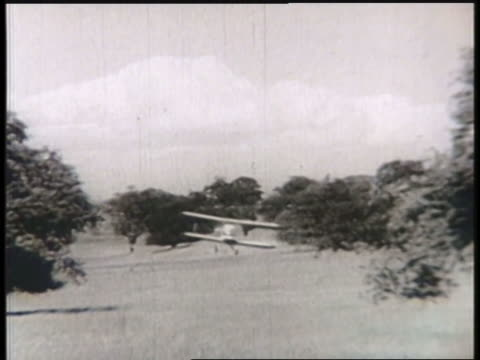 vidéos et rushes de a biplane flies low over fields and forests before crash-landing next to a house. - biplan