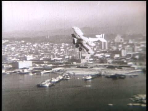 a biplane flies over a coastal city; smoke pours from the engine of a biplane. - 複葉機点の映像素材/bロール