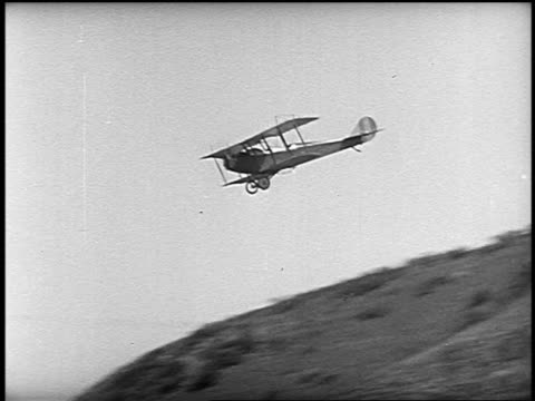 B/W 1953 PAN biplane flying over cliff then crashing into ground