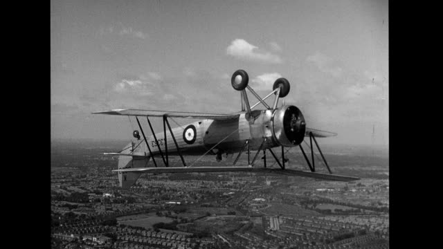 biplane flying upside down over european rural and suburban landscape airtoair footage of biplanes stunt flying on january 01 1930 - acrobatica aerea video stock e b–roll