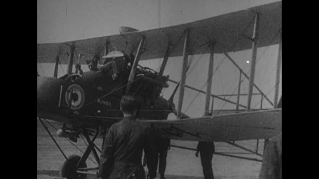 A biplane is pushed from its hangar / a man's hands displaying a small bomb / VS men approach an airplane carrying small bombs and they affix these...