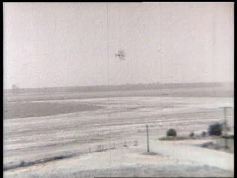 a biplane makes multiple passes over a rural air base. - acrobatica aerea video stock e b–roll
