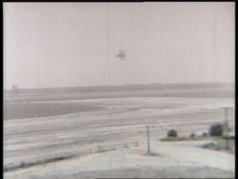 a biplane makes multiple passes over a rural air base. - 複葉機点の映像素材/bロール