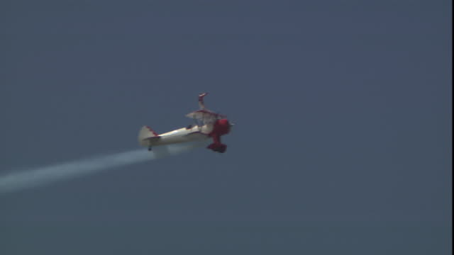 a biplane performs a roll as a stuntperson stands atop the wing. - 複葉機点の映像素材/bロール