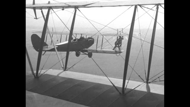 pov biplane piloted by arthur goebel flies without a wheel / the ground crew fastens a wheel to stuntwoman gladys ingle's back and all run to a... - sostituzione video stock e b–roll