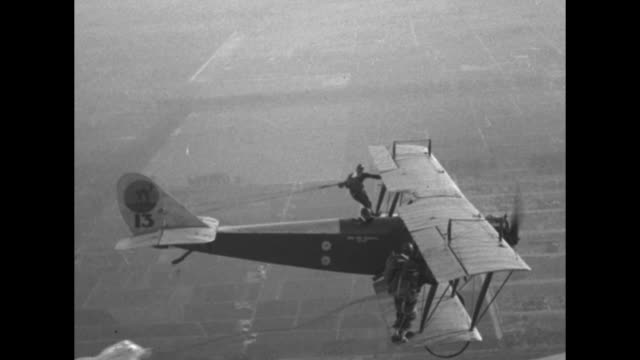biplane rolls forward with two stunt people on bottom wing and one stunt person on top wing / biplane takes off with one stunt person on right wing... - 黒猫点の映像素材/bロール