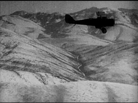 biplane silhouette in flight over mountains valley male pilot into biplane w/ army aviator wings by cockpit unidentified man handing him snowshoes... - 1920年点の映像素材/bロール