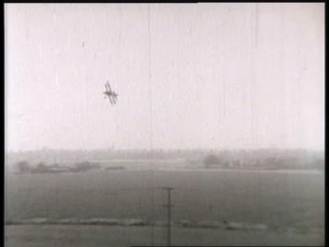 vidéos et rushes de a biplane swoops low over an air base. - biplan