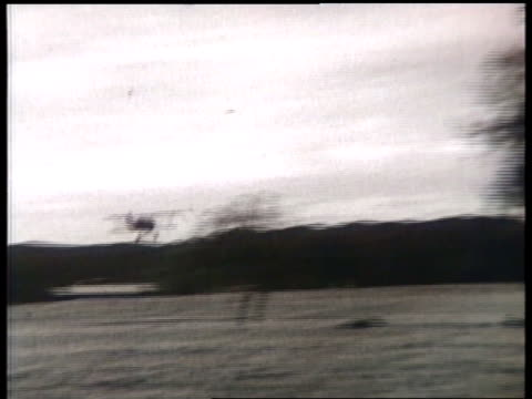 a biplane swoops multiple times over a rural field. - acrobatica aerea video stock e b–roll
