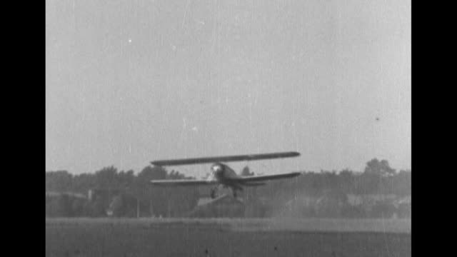 biplane takes off from field, men pulling mailbags from biplane. - 航空便点の映像素材/bロール