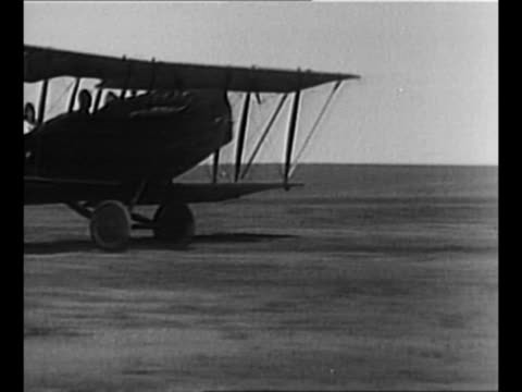 biplane takes off from ground / parachutist heard mcclellan jumps out of plane, falls toward earth / mcclellan, with parachute open, floats over... - biplane stock videos & royalty-free footage