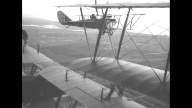 biplane with stunt people ivan unger and gladys ingle standing on upper wing coming towards camera as it takes off / inair shot ingle and unger stand... - aircraft wing stock videos & royalty-free footage