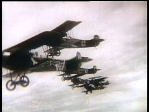 biplanes fly in formation and perform aerial stunts; a pilot shoots down another plane during a dogfight. - acrobatica aerea video stock e b–roll