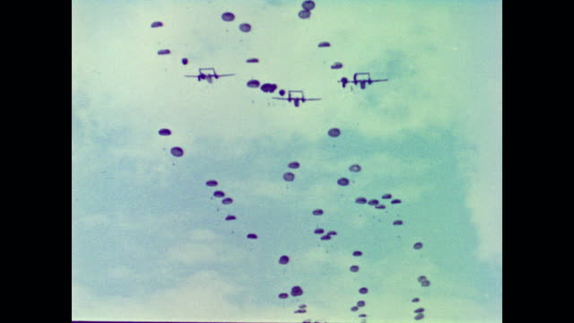 biplanes in clusters of three drop missiles attached to parachutes as they fly across the sky before falling and landing softly on the ground - 1962年点の映像素材/bロール