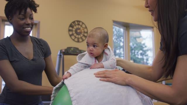 vídeos y material grabado en eventos de stock de biracial bebé tendido sobre una pelota de ejercicios durante una sesión de fisioterapia infantil - fisioterapia deportiva