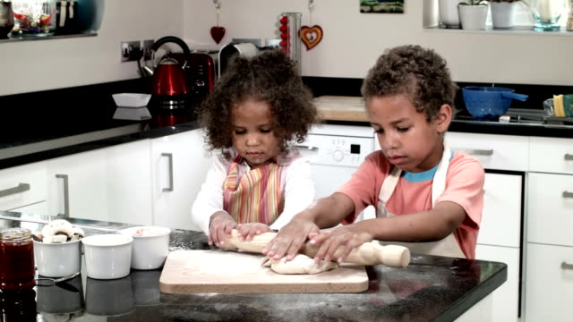 hd: biracial boy and girl rolling dough - kitchenware department stock videos and b-roll footage