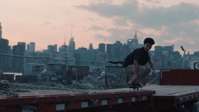 a bi-racial man skateboards infront of the empire state building - nyc - slow motion. - recinzione video stock e b–roll