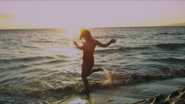 A bi-racial woman playing in the ocean.