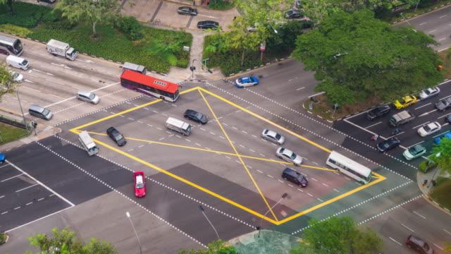 stockvideo's en b-roll-footage met vogel eye view verkeer op kruising road, singapore, time lapse video - dwarsweg