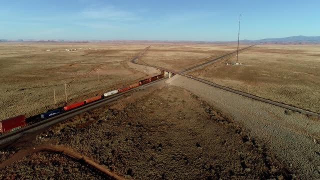 a bird flies over a train crossing the desert of albuquerque new mexico - albuquerque new mexico stock videos & royalty-free footage