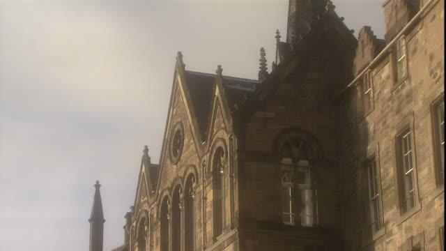 a bird flies past the spire of tolbooth church in edinburgh, scotland. - pinnacle stock videos & royalty-free footage