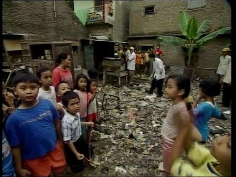 bird flu containment measures; indonesia: jakarta: ext lms chickens wander about alley with children playing in b/g young boys playing in alleyway... - b rolle stock-videos und b-roll-filmmaterial