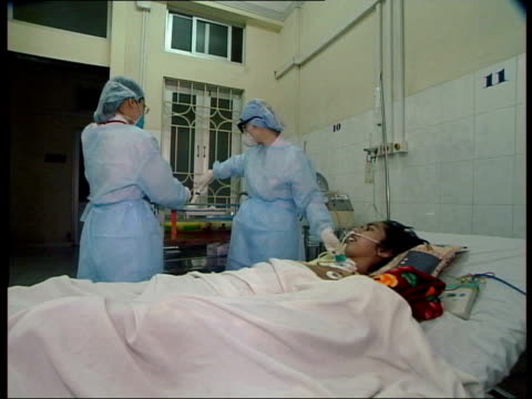 bird flu spreads to russia; tx 4.5.2004 vietnam: hanoi: int nurses treating bird flu sufferer - avian flu virus stock videos & royalty-free footage