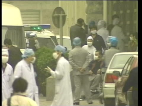 bird flu threat; lib ???: ext people in caps, gowns and masks outside hospital during sars outbreak - 重症急性呼吸器症候群点の映像素材/bロール