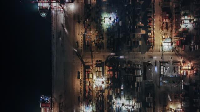 vidéos et rushes de vue d'oiseau t/l du port industriel avec le navire de récipients la nuit - être ancré