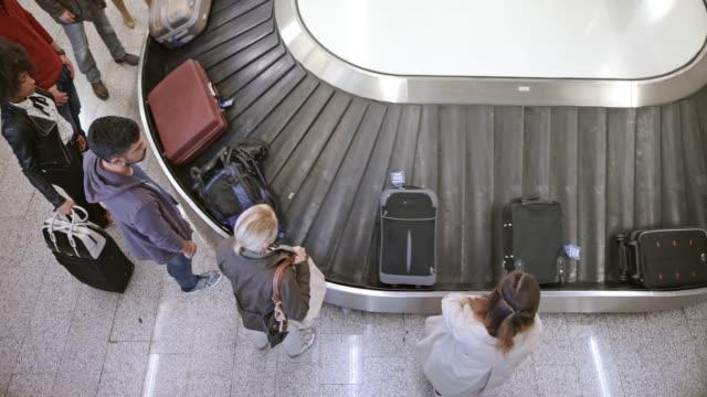 TIME-LAPSE Bird view van passagiers op de luchthaven het oppakken van hun bagage van de carrousel
