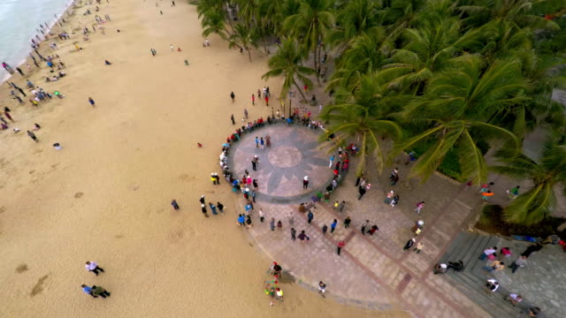 bird's eye perspective of beach in sanya, hainan province, china. drone shot moving down on people dancing - spoonfilm stock-videos und b-roll-filmmaterial