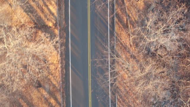 bird's eye view along two-lane road on a winter day in new york - ニューパルツ点の映像素材/bロール