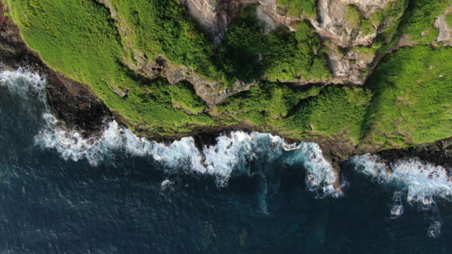 vidéos et rushes de birds eye view flying over rocky coastline - cliff