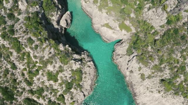 birds eye view following a turquoise river in zakynthos, greece. - greek islands stock videos and b-roll footage