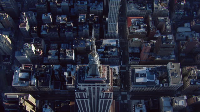 bird's eye view looking down at the top of the empire state building. the skyscraper is one of the most famous landmarks in new york city, new york, usa. - ganz oben stock-videos und b-roll-filmmaterial