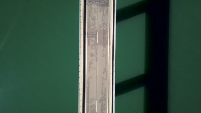 birds eye view of a bridge and empty road over a water reservoir - empty road stock videos and b-roll footage