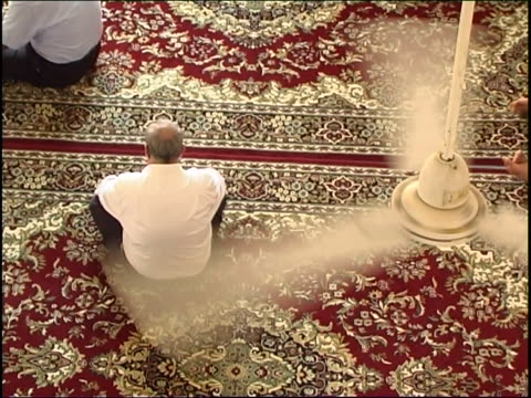 bird's eye view of a shia man sitting on the carpeted floor of a mosque under a ceiling fan. - shi'ite islam stock videos & royalty-free footage