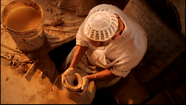 bird's eye view of a traditional potter throwing a clay pot on his potter's wheel. - pottery stock videos & royalty-free footage