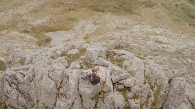 Birds eye view of a woman taking pictures on the top of a mountain
